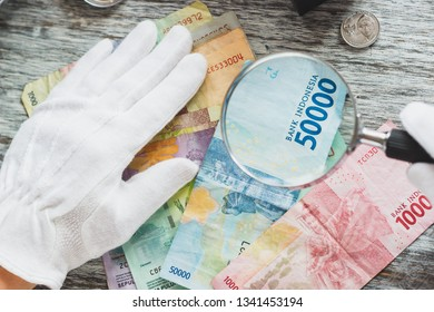 Hands in white gloves, different Indian rupiahs, numismatics concept, blurred background