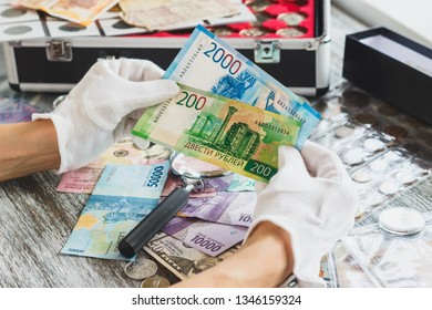 Hands in white gloves, different Russian rubles, numismatics concept, blurred background