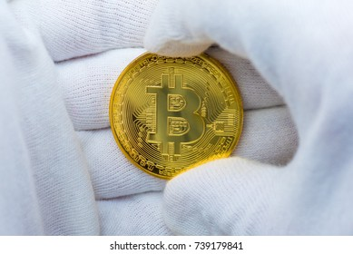Hands with white gloves holding a golden bitcoin