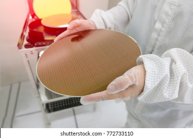 Hands in white gloves holding moving a silicon wafers for production, semiconductor. select focus, blurred background
