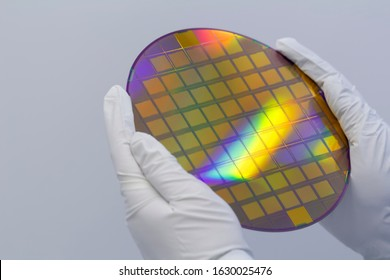 Hands in white gloves holding a silicon wafer on a white background.
