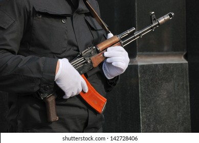 hands in white gloves with a Kalashnikov assault rifle
