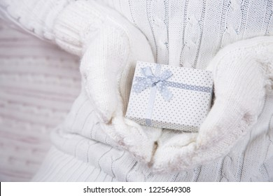Hands in white knitted mittens holding cute gift box. Christmas present. New Year card.