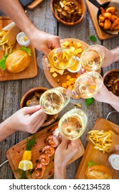 Hands with white wine toasting over served table with food. Friends Happiness Enjoying Dinning Eating Concept.