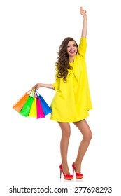 Hands Up Who Goes Shopping With Me. Laughing elegance young woman in red high heels and yellow mini dress holding colorful shopping bags and rising arm. Full length studio shot isolated on white.