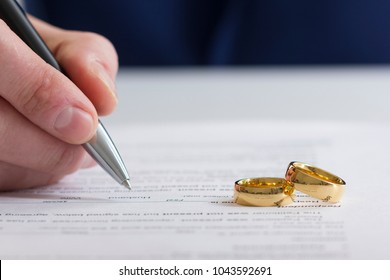 Hands of wife, husband signing decree of divorce, dissolution, canceling marriage, legal separation documents, filing divorce papers or premarital agreement prepared by lawyer. Wedding ring