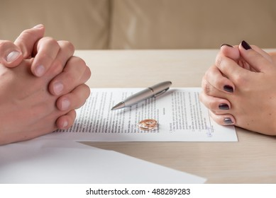 Hands of wife and husband signing divorce (dissolution, canceling marriage, legal separation) documents, filing divorce papers or premarital agreement prepared by lawyer. Wedding ring in the center