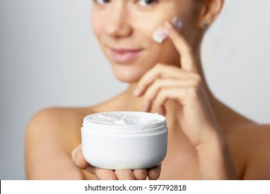 Hands of a woman about to apply face cream. Holding Moisturizing Lotion.Close-up young beautiful face of girl applying moisturize cream