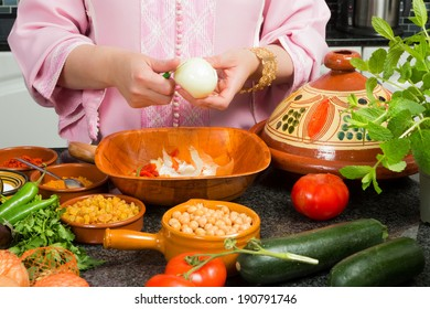 Hands of a woman adding onions to a traditional Moroccan tajine during Ramadan nights (Moroccan immigrant woman in modern European kitchen)