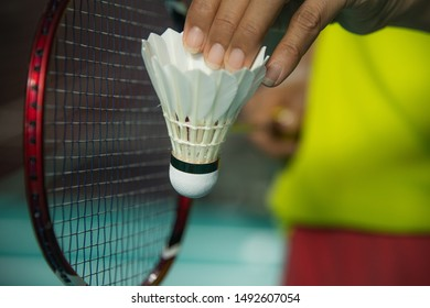 Hands of woman BADMINTON player in green sport shirt and red skirt holding shuttlecock and racket ready to serve with blur Badminton court background.