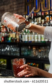 Hands of woman bartender making an alcohol cocktail at the bar
