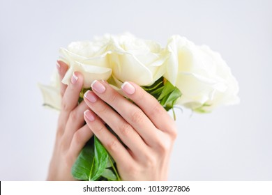 Hands of a woman with beautiful french manicure and bouquet of white roses