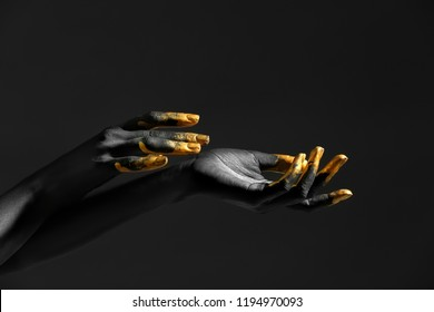 Hands of woman with black and golden paint on her skin against dark background