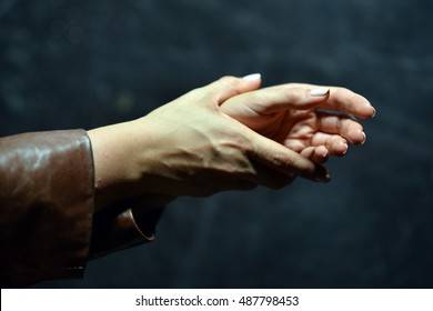 Hands of a woman in a brown leather coat. Hands clasped together. Beautiful manicure.
