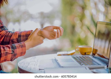 Hands of woman with carpal tunnel syndrome over computer keyboar