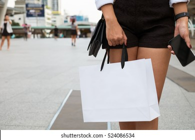 Hand's woman carry white shopping bag and holding a smart phone when she go to shopping.