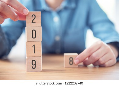 Hands of woman change wood cube text 2018 to new year 2019.