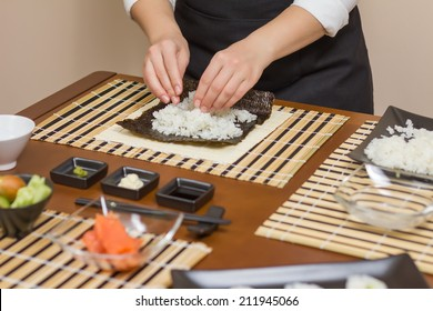 Hands of woman chef filling japanese sushi rolls with rice on a nori seaweed sheet. Selective focus in sushi roll.