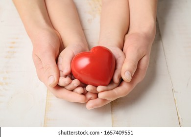 Hands of woman and child with red heart on wooden background. Cardiology concept