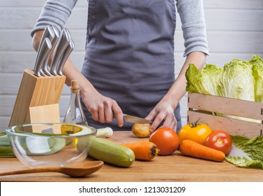 The hands of a woman cook prepare a salad with fresh vegetables. Healthy food. White background