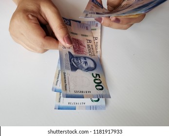 hands of a woman counting mexican banknotes of 500 pesos