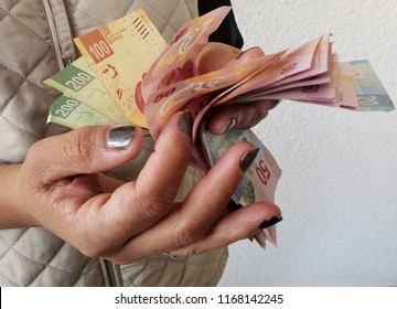 hands of a woman counting mexican bills