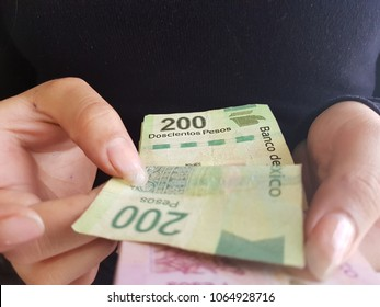 hands of woman counting mexican peso bills
