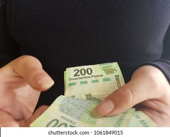 hands of woman counting money, Mexican 200 Peso bills