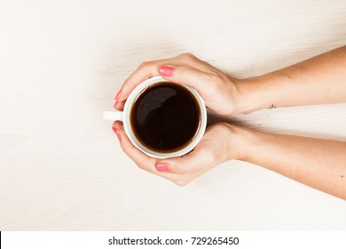 hands of woman with cup of coffee