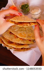 Hands of a woman eating a Quesadilla of pork and melted cheese in a tortillas.