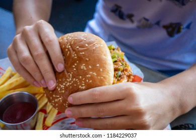 Hands of woman eating sloppy burger.