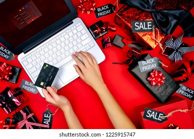 Hands of woman female adult with credit debit card and laptop making payment buying new goods with sale and discount on black friday holiday on red background with presents and black sale labels