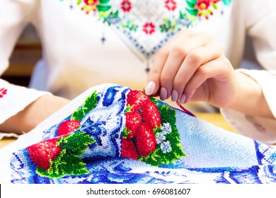 Hands of woman / female / girl in traditional ukrainian shirt sewing ornament. Embroidery concept
