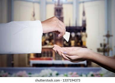 Hands of a woman getting holy communion bread from a priest during celebrating a mass in the church