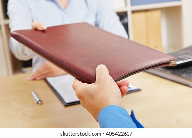 Hands of woman giving application portfolio to HR man in office