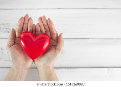 Hands of Woman hold red heart over wood white background. Health Care , Love , CSR  Concept.