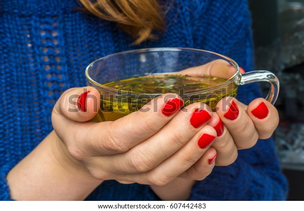 Hands of woman holding cup of hot green tea