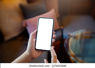 hands of woman holding empty white mobile smart phone.