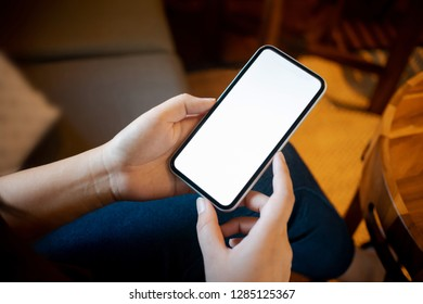 hands of woman holding empty white screen mobile phone.