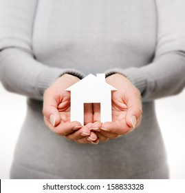 Hands of woman holding paper house
