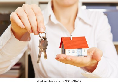 Hands of a woman holding two keys and a small house
