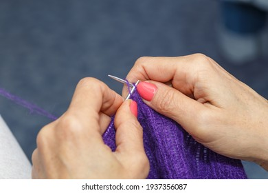 hands of woman knitting handmade clothes with spokes using  wool yarn. Concept of leisure activity.Knitting from yarn on  coarse spokes.