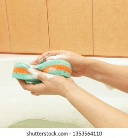Hands of woman lathering a green sponge with soap
