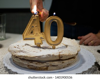 hands of a woman lighting Golden candles four and zero of a birthday cake celebrating 40th aniversary