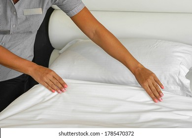 Hands of woman maid making bed in hotel room. Housekeeper Making Bed