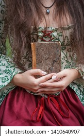 Hands of woman in medieval dress holding the old vintage book