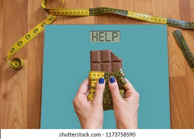 Hands of woman with on weighing scale asking for help to avoid the temptation to eat sweets. Stop eating sweets, healthy diet concept with measurement tape rolled on chocolate above weight scale