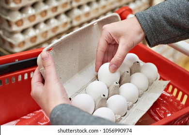 Hands woman with packages of white eggs in the store