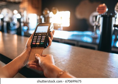 Hands of woman paying bill using a credit card at bar. Cropped shot of female at brewery factory doing cashless payment.