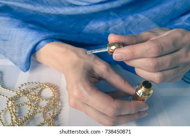 Hands of a woman with perfume. Arab woman opening perfume bottle.